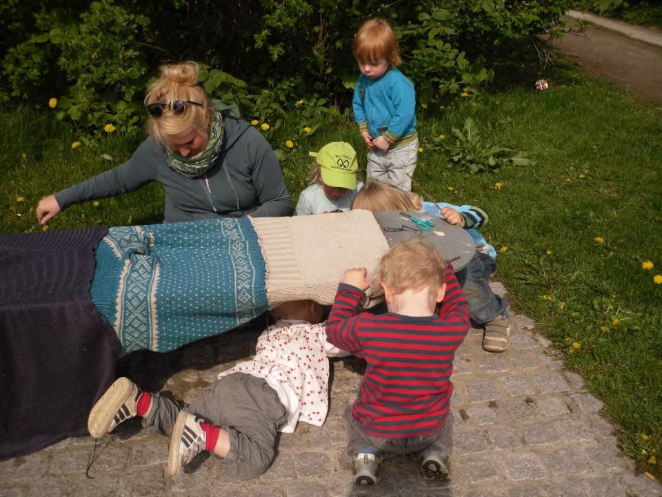 Barn og voksne kler en benk med tøy.