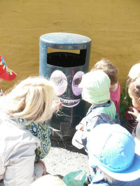 Barn og voksen dekorerer søppelkasse med øyne og munn.