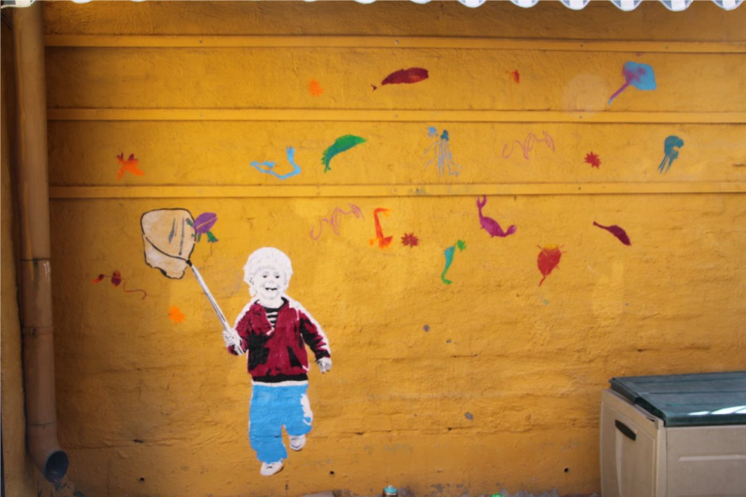 Vegg i busskur dekorert med barnetegninger.