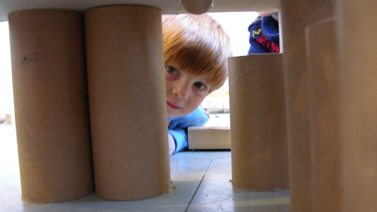 Gutt som titter fram mellom konstruksjon av papprør.