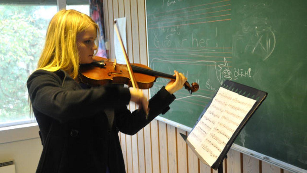 Jente som spiller fiolin foran et notestativ med noter.