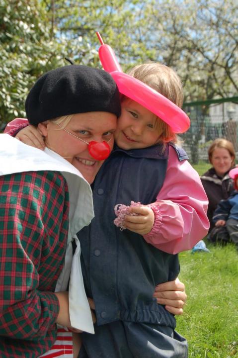 Voksen dame utkledd som klovn Barn med ballongdyr på hodet.