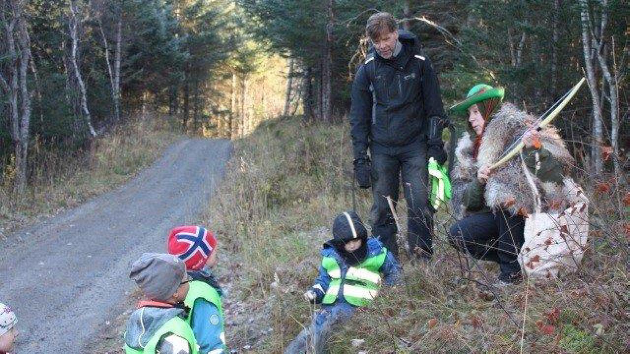 Barn og voksne ute i naturen. En voksen har på seg kostyme.