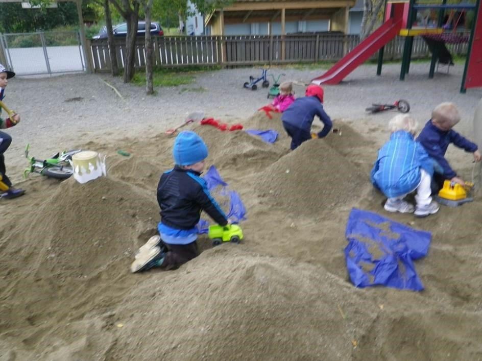Barn leker i sandkasse.