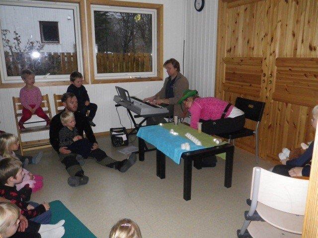 Samlingsstund i barnehagen. Barn og voksen sitter i en ring på gulvet. En voksen spiller piano.