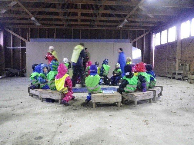 Barn og voksne sitter i en ring på benker.