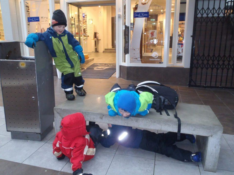 Barn leker ved benk i byen.