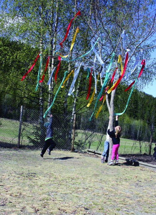 Barn står ved et tre som har fargerike strimler festet på greinene.