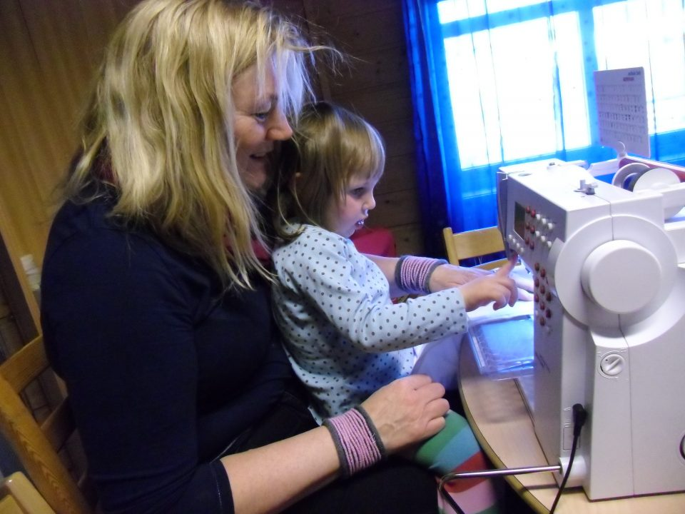Et barn sitter på fanget til en voksen foran en symaskin.