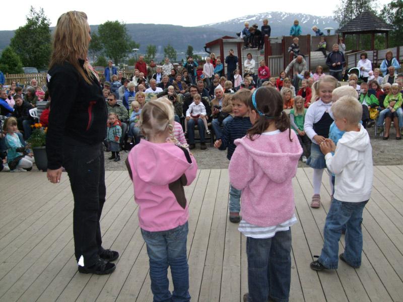Barn som står på scenen foran en stor folkemengde.