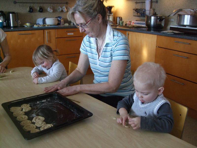 Barn sitter ved et bord og baker sammen med en voksen.