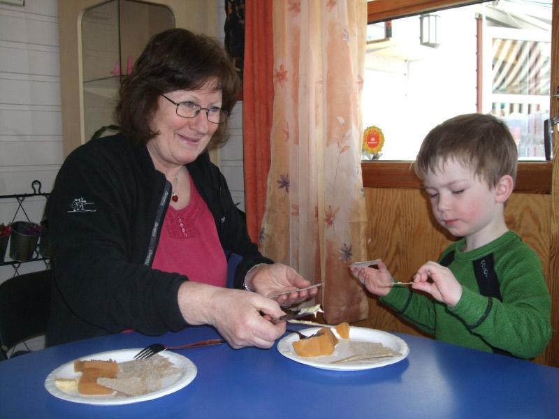 Et barn og en voksen sitter ved et bord og spiser tradisjons mat.