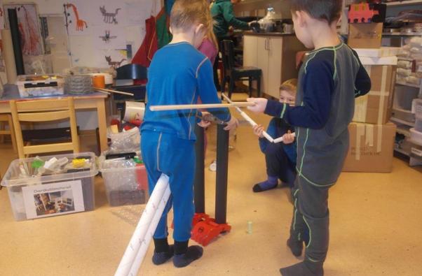 Barn bygger med gjenbruksmateriale.