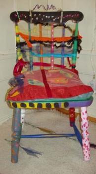 Fargerik stol dekorert med stoff og garn.