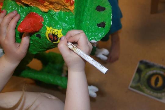 Deltaljer, maling og fargelegging av dinosaurens hode.