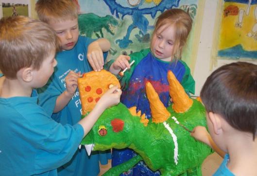 Barn samarbeider om å male en dinosaurskulptur.