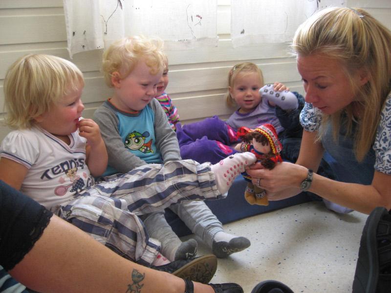 En voksen holder en dukke med samisk kofte opp foran en barnegruppe i samlingsstund i barnehagen.