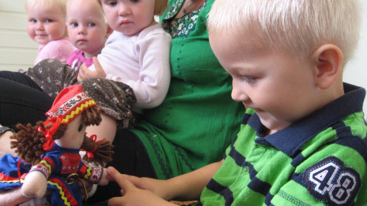 Et barn holder en dukke med samisk kofte.