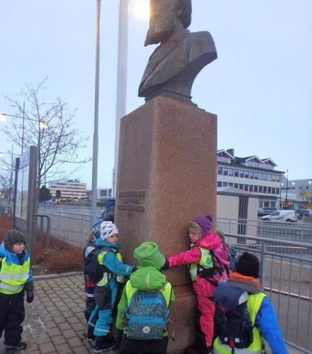 Barn som studerer skulptur i byen.