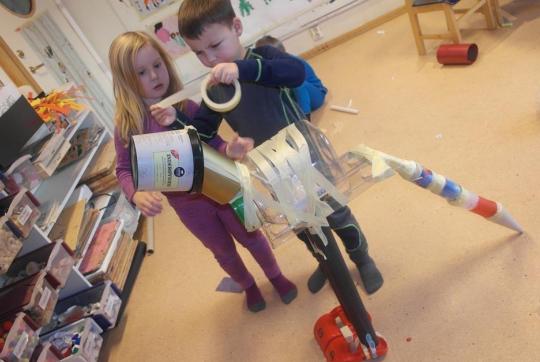 Barn bygger dinosaur av gjenbruksmaterialer.