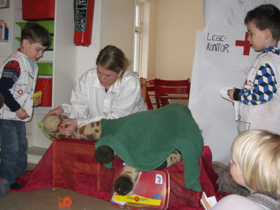Kosedyrsjiraff får gehandling av sykepleier.