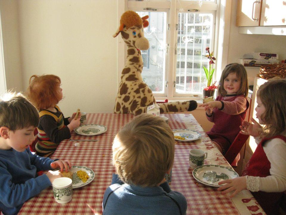 Barn sitter rundt et bord ved måltidet, en giraff sitter ved enden av bordet.