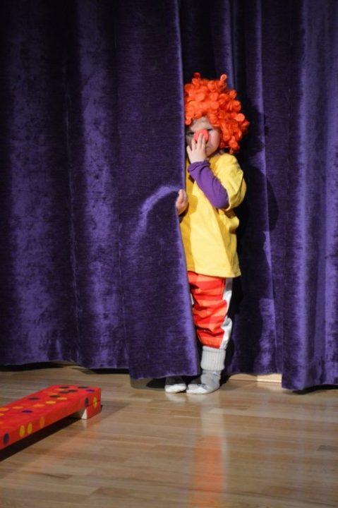 Sjenert barn i klovnekostyme gjemmer seg bak sceneteppe.