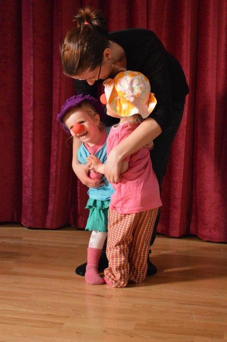 Kvinne holder rundt to barn som har klovnekostyme på seg.