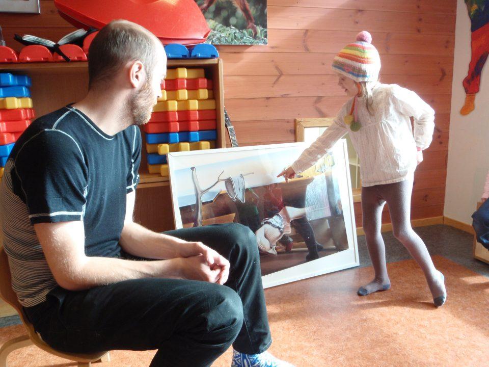 Barn og voksen studerer kunstbilde.