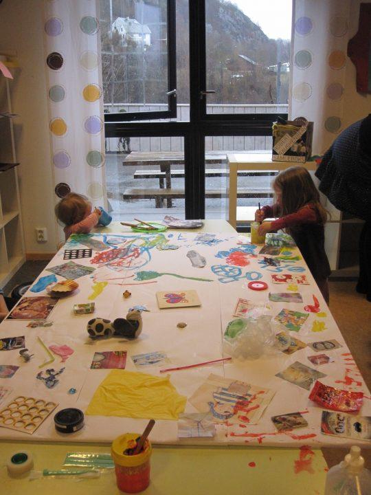 Barn som lager kunst ved et bord.