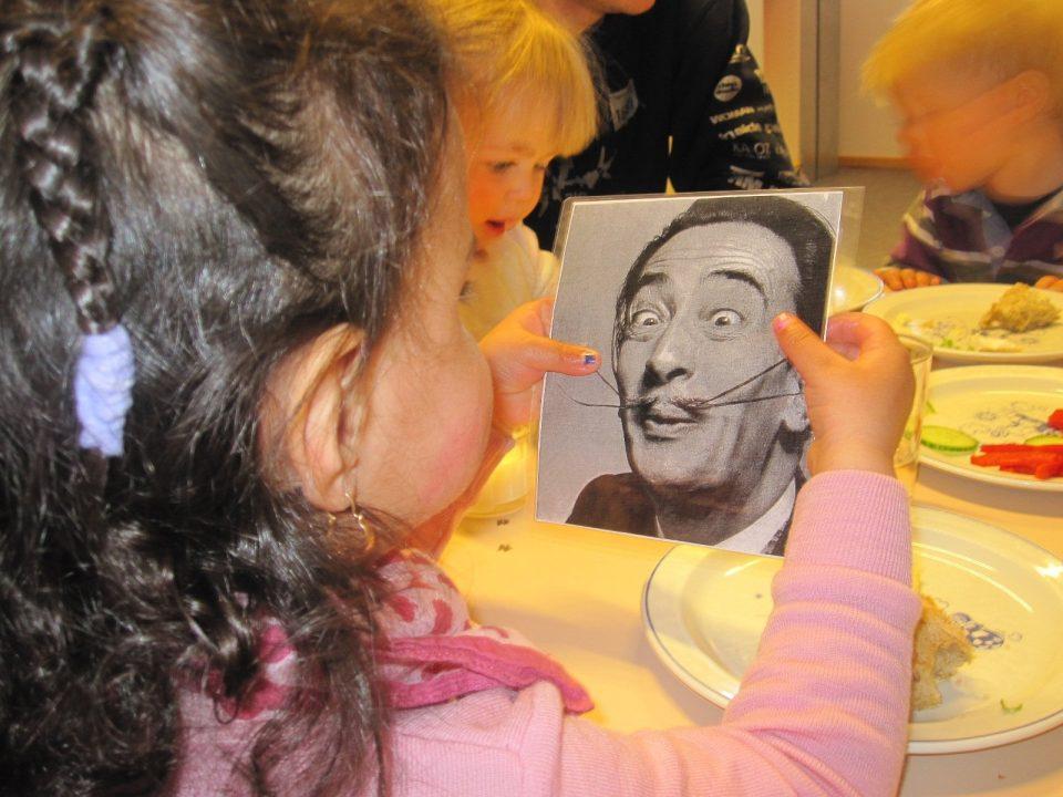 Barn holder fotografi av herre med morsom bart.