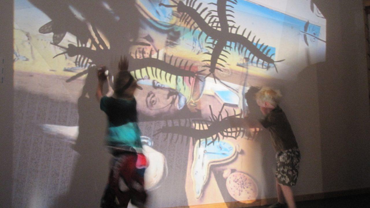 Barn som danser og eksperimenterer med lys mot vegg.