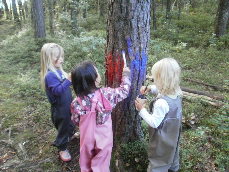 Barn maler på et tre i skogen.
