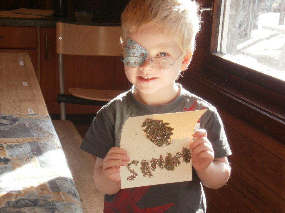 Gutt holder opp bilde laget av naturmateriale.