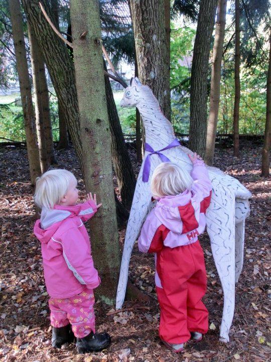 To barn titter på et dyr som står i skogen.