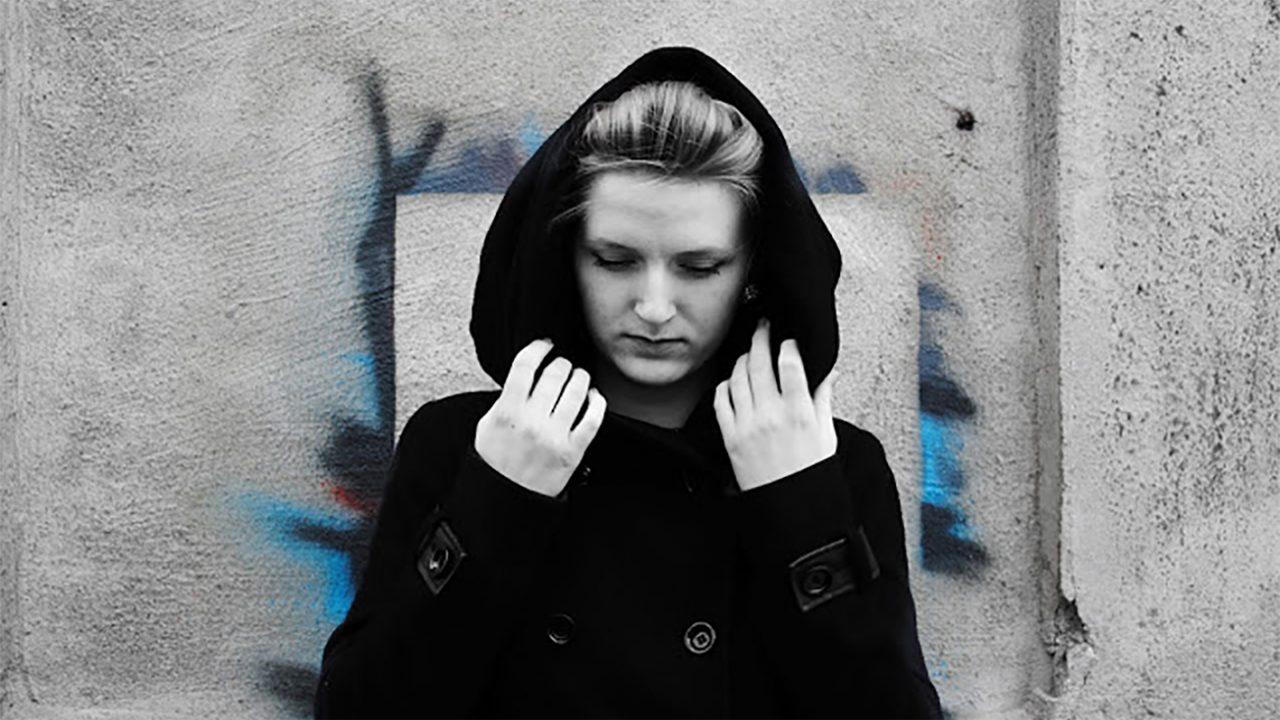 Sort/hvitt portrett av ung jente med sort jakke og hette over hodet. Jenta er fotografert mot murvegg med grafitti.