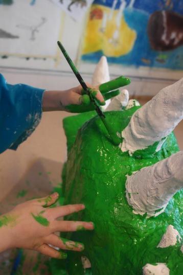 Barn maler grønn maling på gipsskulptur.