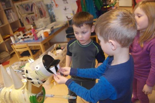To gutter setter tenner på dinosaurskulptur.
