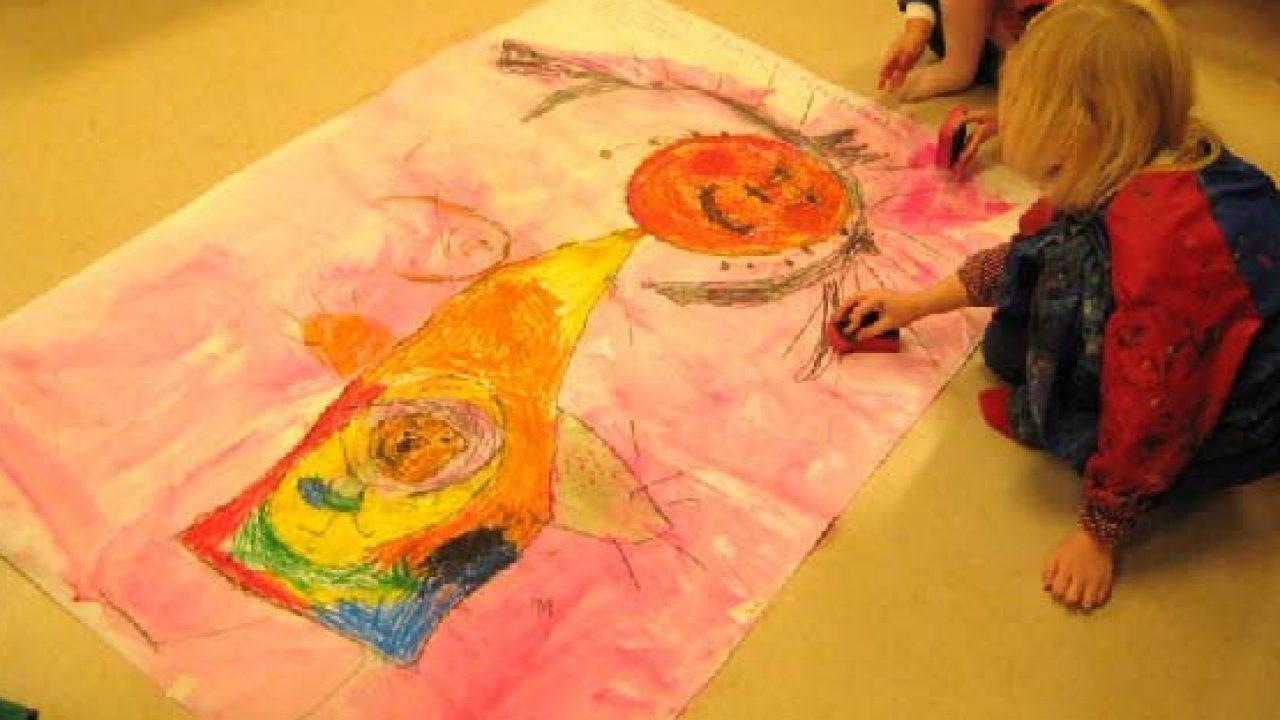 Barn lager fellesbilde på stort ark på gulvet.