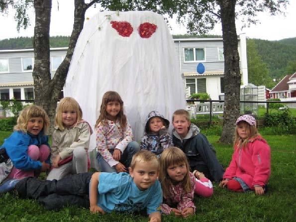 Barn foran skulptur som ser ut som et spøkelse.
