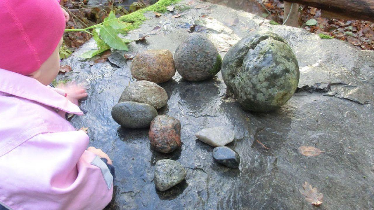 Barn studerer små steiner som ligger på en stor stein.