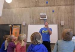 Mann som sjonglerer med blå baller foran barna.