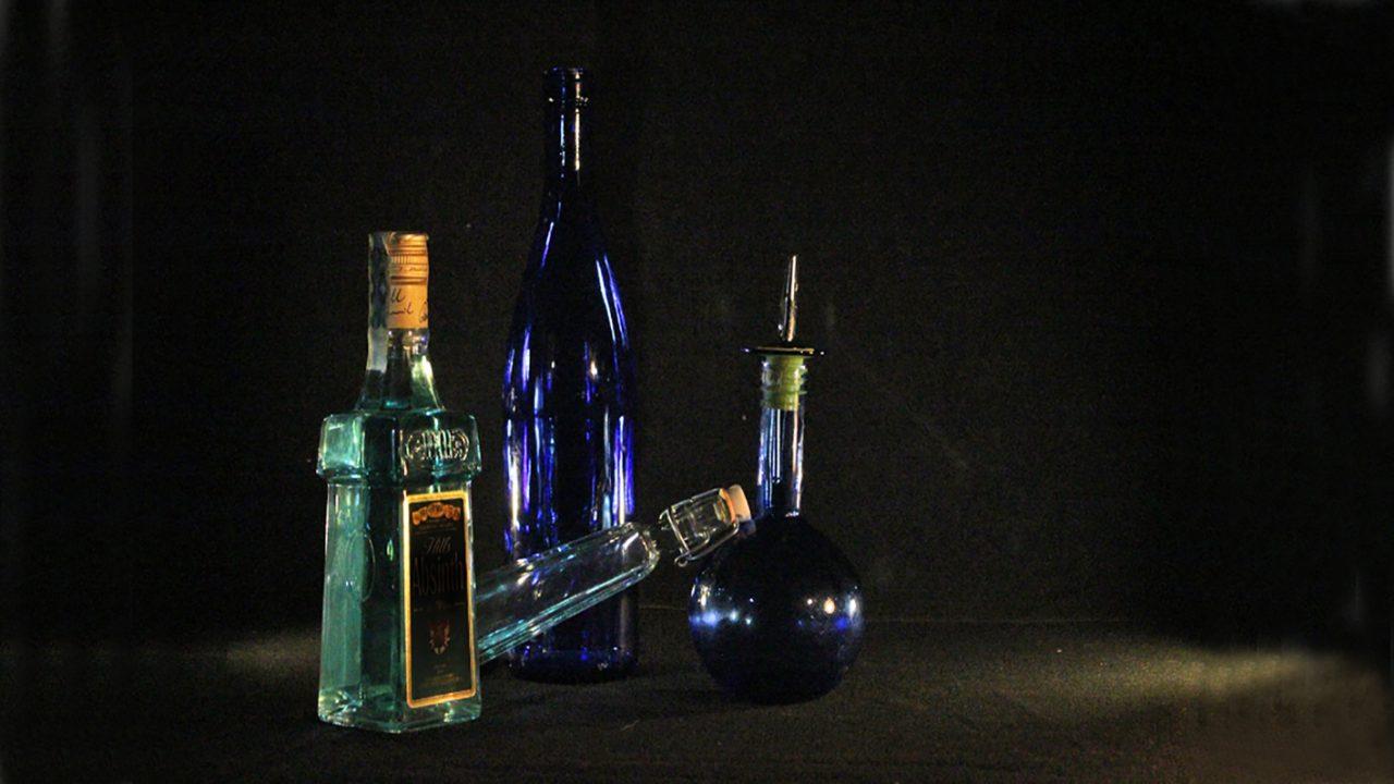 Komposisjon av grønne og blå glassflasker mot sort draperi, elevfoto.