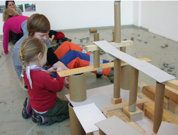 Barn og voksen som bygger konstruksjoner av papprør og planker.