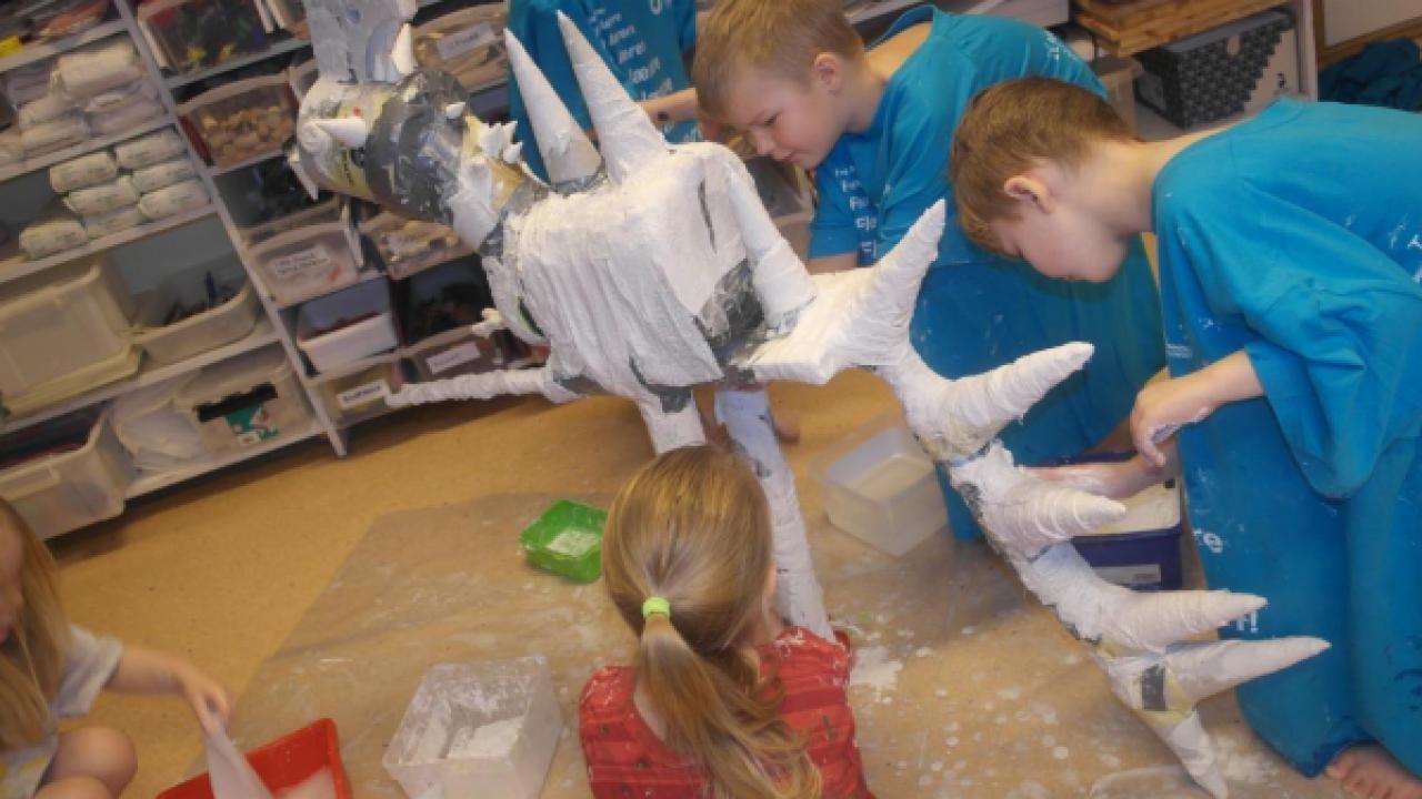 Barn som lager gipsskulptur.