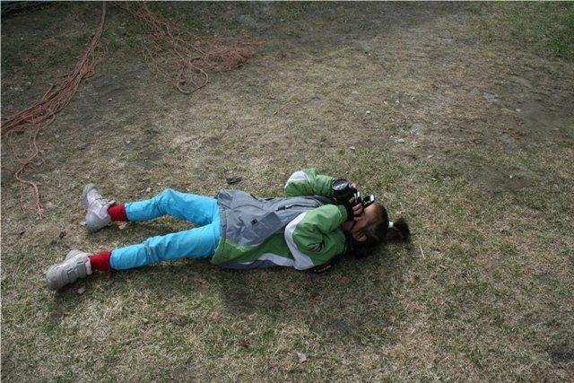 Et barn ligger på bakken mens hun fotograferer.