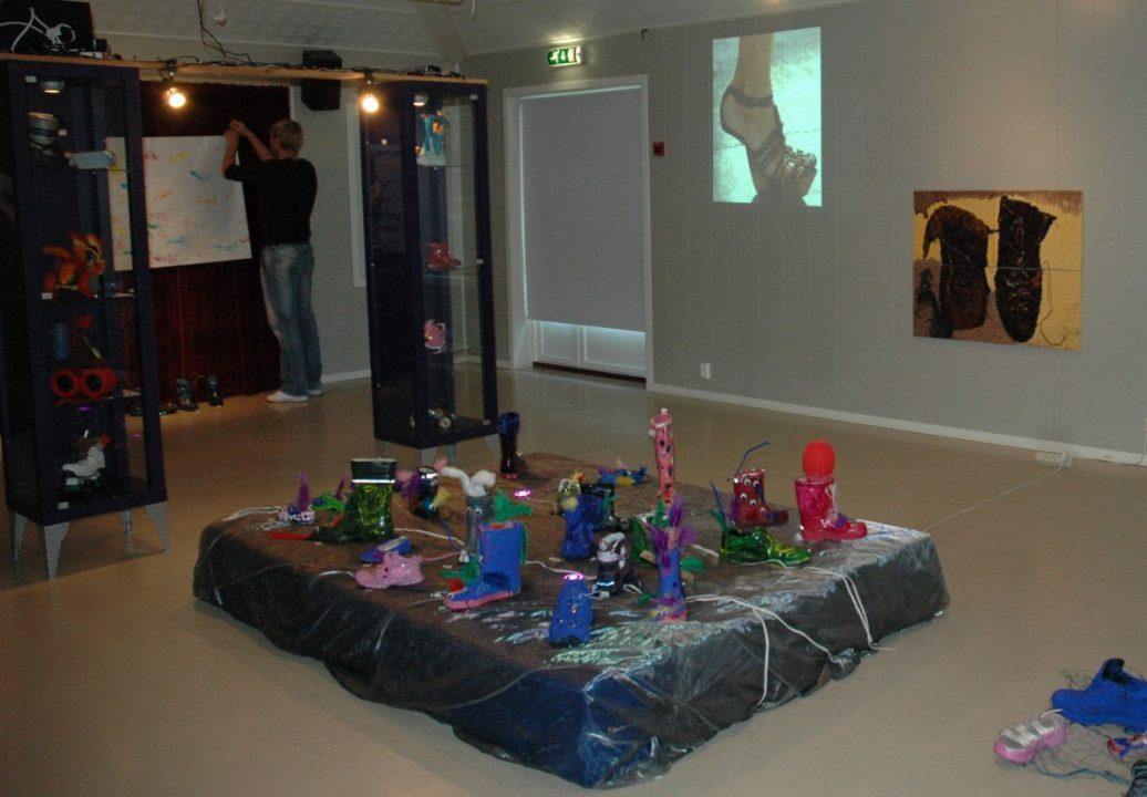 Utstilling av barnekunst, sko i ulike farger på et podie.