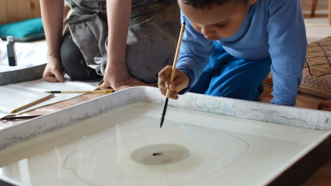 Gutt dypper pensel i kar fylt med vann.