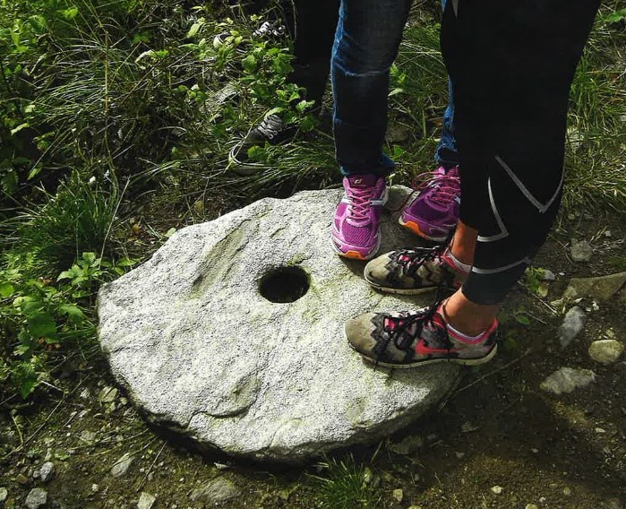 Fire føtter som står på en kvernstein.