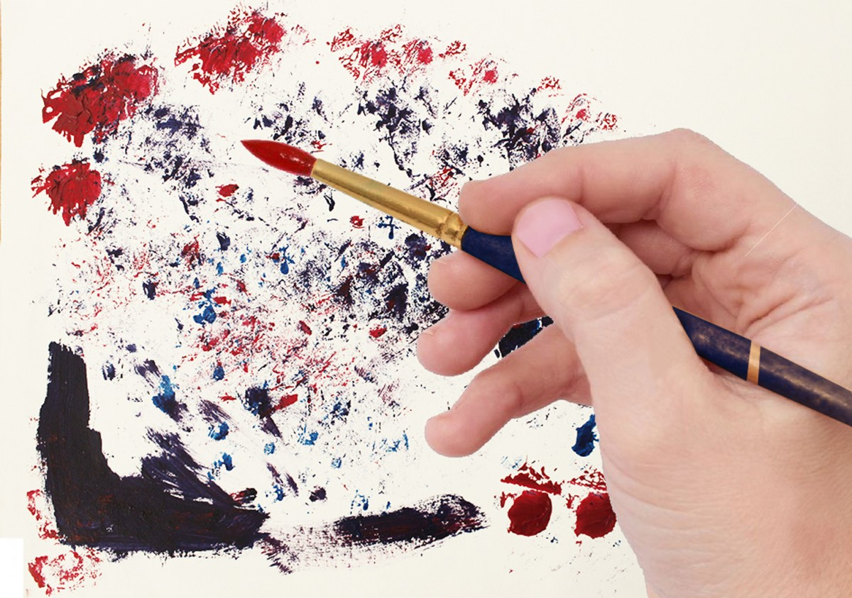 Hånd med pensel og malingsflekker